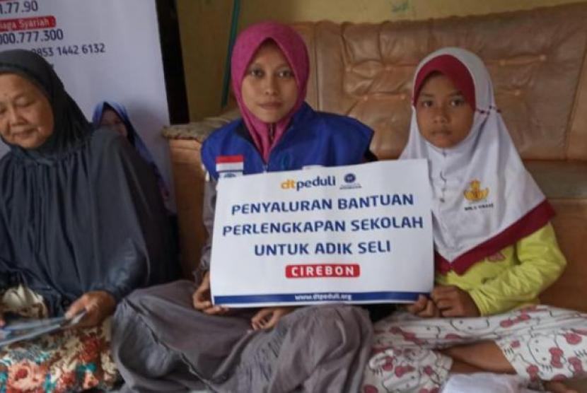 Seli Rahmawati (kanan), siswi kelas 5 SD Impress Cisaat, saat menerima bantuan DT Peduli didampingi oleh neneknya.
