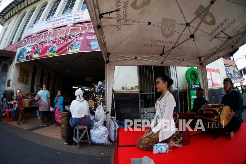 Seniman dari Dinas Kebudayaan (Disbud) Kota Solo menghibur pengunjung dan pedagang di Pasar Gede Solo, Jawa Tengah, Kamis (15/4/2021). Pemerintah Kota Solo menghadirkan hiburan tradisional Siteran tersebut untuk meningkatkan jumlah kunjungan pembeli dan menarik wisatawan di Pasar Gede Solo.