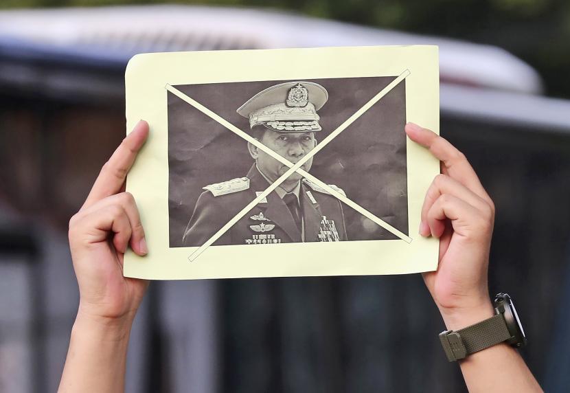 Seorang aktivis memegang potret Panglima Tertinggi Myanmar Jenderal Min Aung Hlaing yang rusak saat rapat umum menentang kudeta militer di Jakarta, Indonesia, Sabtu, 24 April 2021.