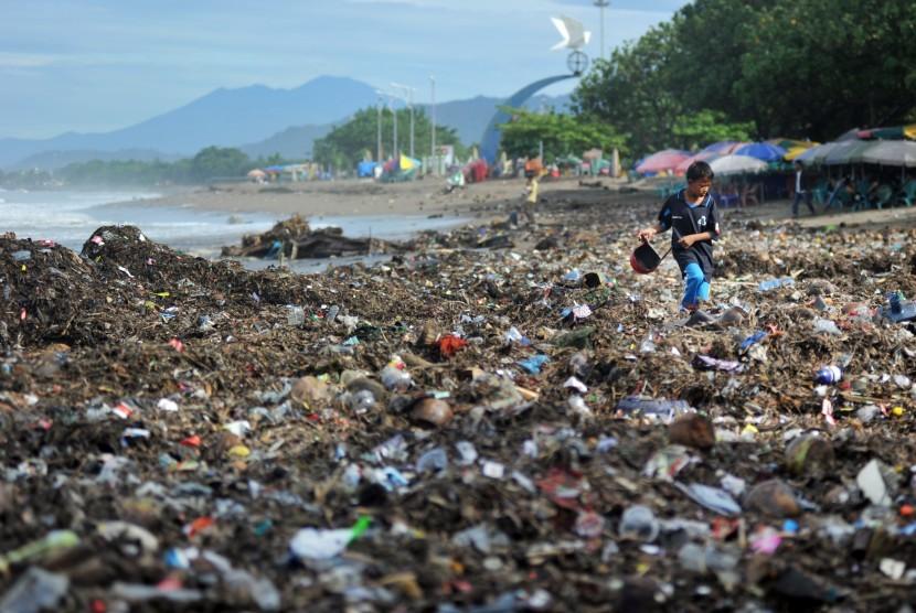 Seorang anak berjalan di atas tumpukan sampah plastik yang berserakan di Pantai Padang, Sumatera Barat, Selasa (22/1/2019).