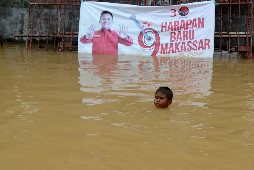 Seorang anak bermain di lokasi banjir di Perumahan Bumi Bung Permai, Makassar, Sulawesi Selatan, Kamis (24/01/2019).