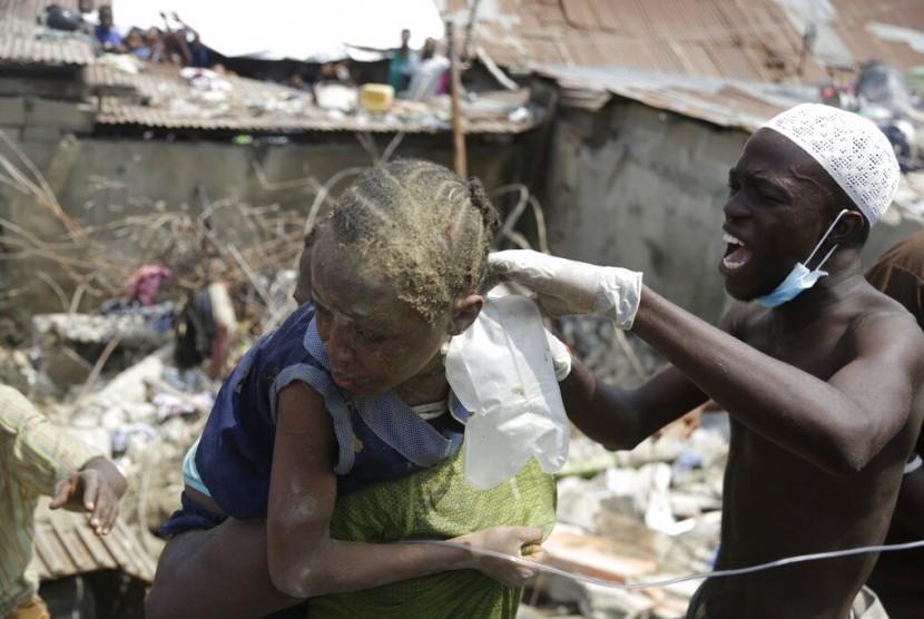 Seorang anak diselamatkan dari reruntuhkan bangunan yang ambruk di Lagos, Nigeria, Rabu (13/3).