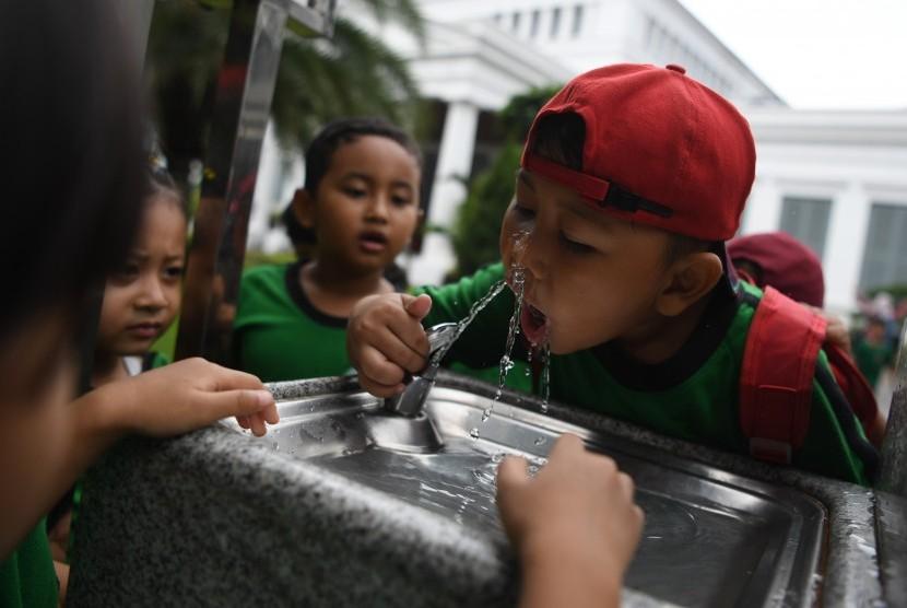Seorang anak meminum air secara langsung dari kran milik PT PAM Lyonnaise Jaya (Palyja) di Museum Nasional, Jakarta, Rabu (13/2/2019).