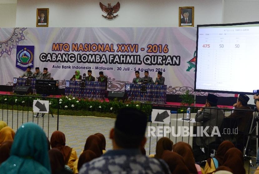 Seorang anak memotret tiga grup Kafilah yang mengikuti final MTQ Nasional ke XXVI cabang Fahmil Quran (Cerdas Cermat) di Aula Bank Indonesia, Kota Mataram, Nusa Tenggara Barat, Kamis (4/8).
