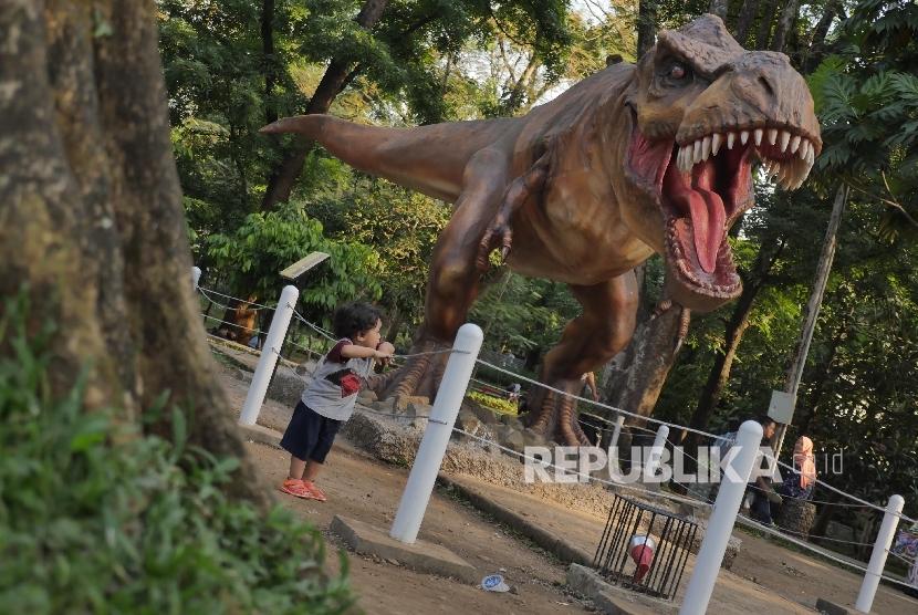 Seorang anak memperhatikan patung dinosarus T-Rex di Taman Lansia Bandung, Selasa (2/8).