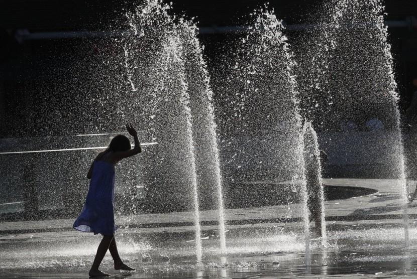 Seorang anak mendinginkan diri di sebuah air mancur di Milan, Italia, Senin (24/6). Gelombang panas ekstrem mulai menerjang Eropa.