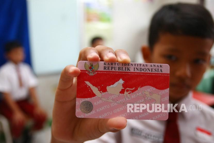 Seorang anak menunjukan Kartu Identitas Anak (KIA) miliknya.