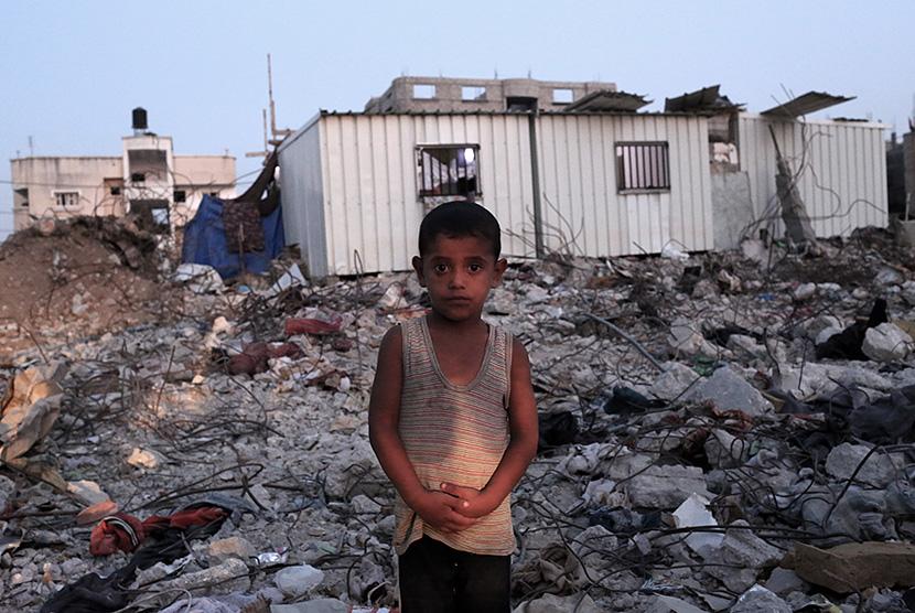 Seorang anak Palestina berdiri di depan rumahnya yang hancur akibat serangan udara Israel di Kota Gaza, Palestina.