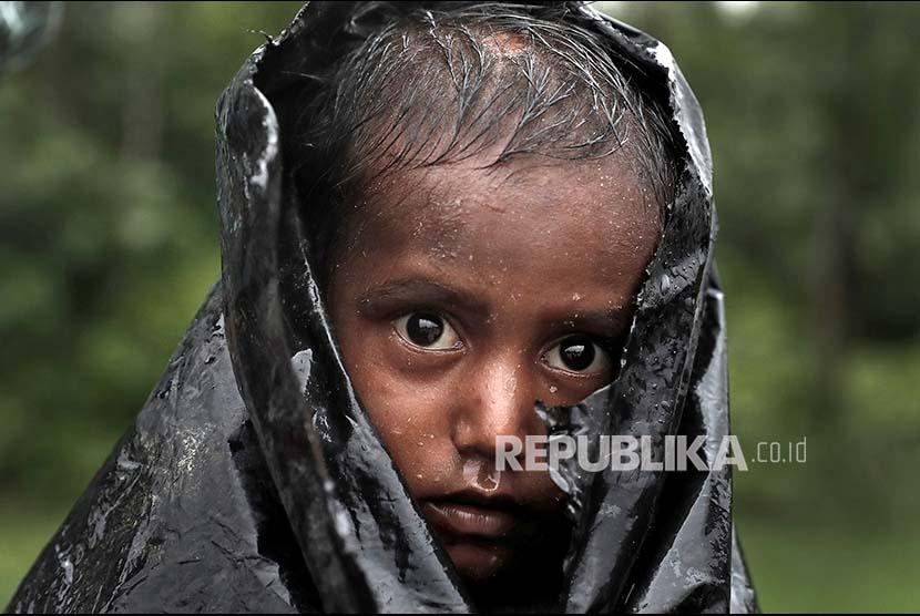 Seorang anak Rohingya menunggu bantuan internasional di kamp pengungsi Cox Bazaar, Bangladesh.
