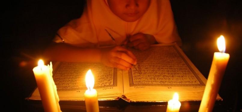 Seorang anak sedang membaca ayat suci Alquran mengunakan lilin/ilustrasi