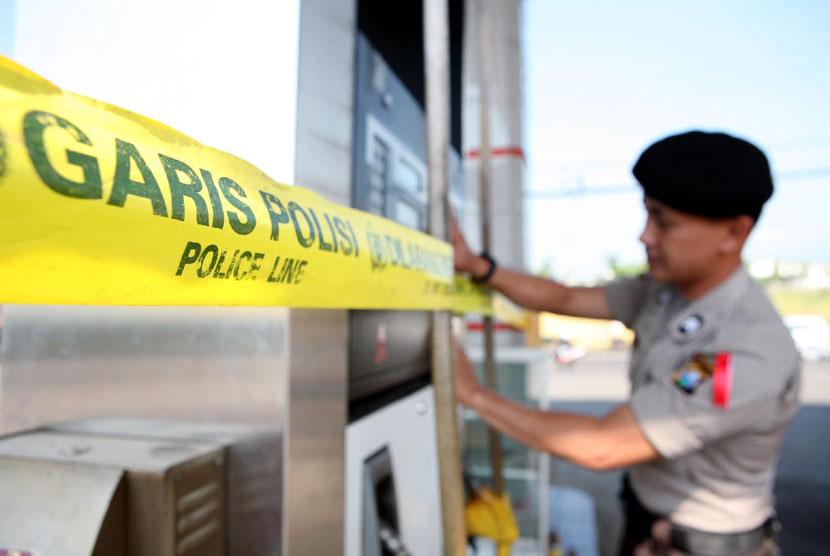 Seorang anggota petugas memasang garis polisi.   (ilustrasi)