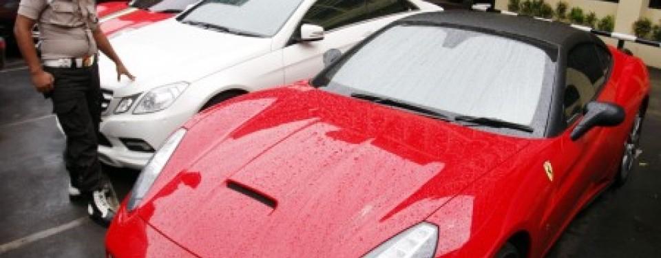 Seorang anggota polisi mengamati tiga buah mobil mewah Ferrari dan Mercedes Benz milik tersangka pembobol nasabah Citibank, Melinda Dee alias Inong Melinda