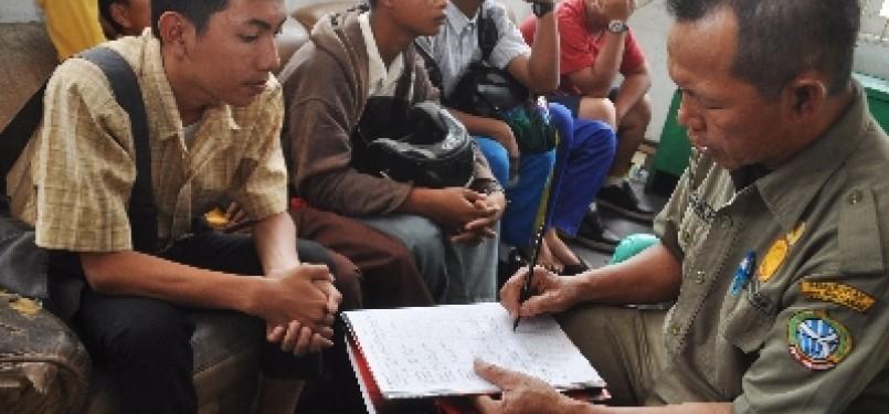 Seorang anggota Satuan Polisi Pamong Praja (Satpol PP) mendata sejumlah pelajar sekolah yang terjaring saat razia pelajar (ilustrasi).