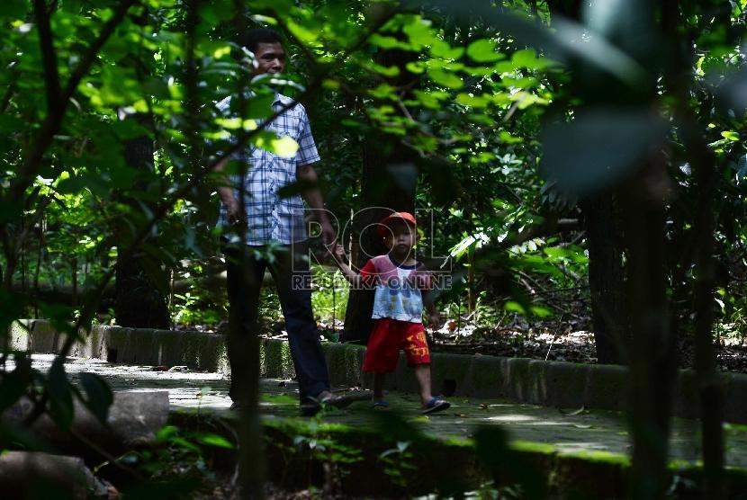 Seorang ayah bersama anaknya menikmati tumbuhan yang terdapat di Hutan Kota Srengseng, Pengumben, Jakarta Barat, Kamis (12/3). (Republika/Raisan Al Farisi)