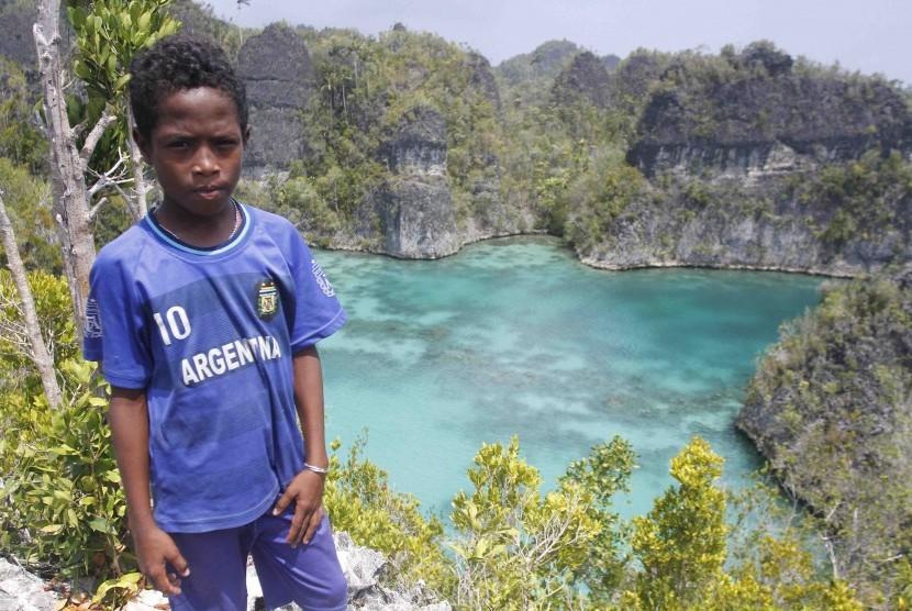 Seorang bocah berpose dengan latar belakang telaga bintang di Raja Ampat, Papua Barat, Senin (2/11).