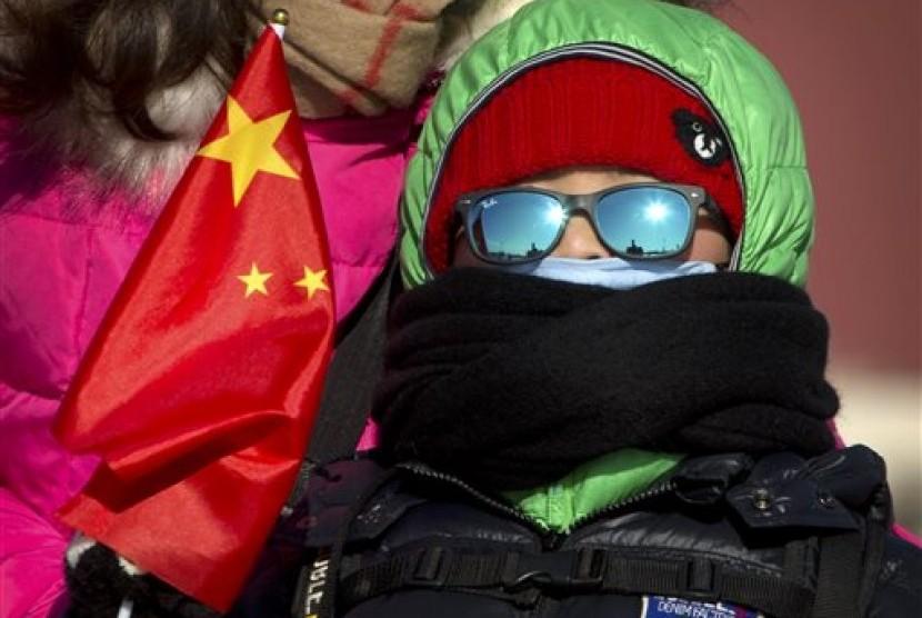 Seorang bocah laki-laki dengan memegang bendera Cina di Lapangan Tiananmen di Beijing, Sabtu, 23 Januari 2016. Suhu dingin di Beijing mencapai titik terendah dalam 30 tahun, yakni minus 17 derajat Celcius.