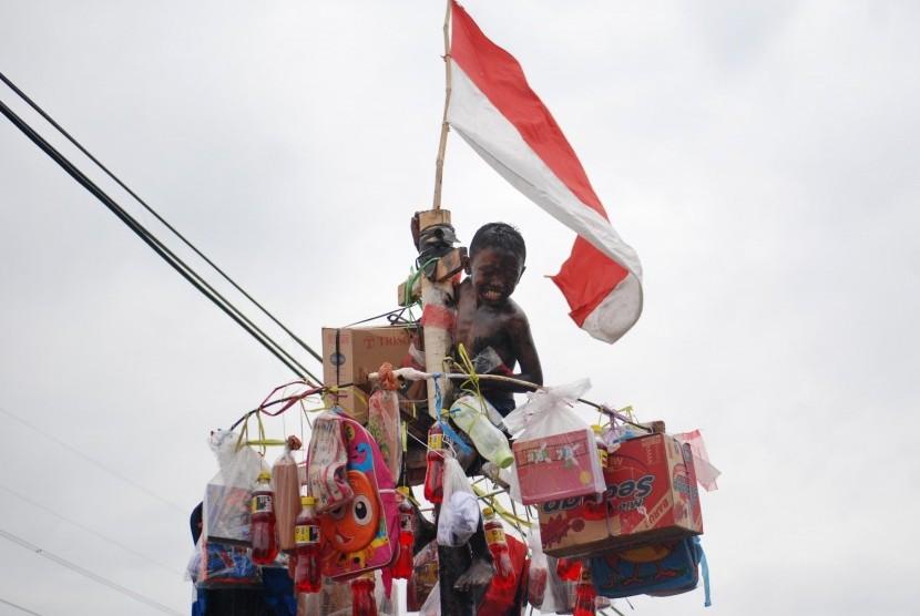 Seorang bocah mengikuti lomba panjat pinang memperingati HUT Kemerdekaan ke-72 RI (Ilustrasi)