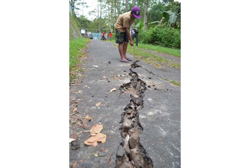 Seorang bocah menunjukkan jalan yang retak akibat gempa bumi di Desa Klangon, Madiun, Jatim, Jumat (26/6).