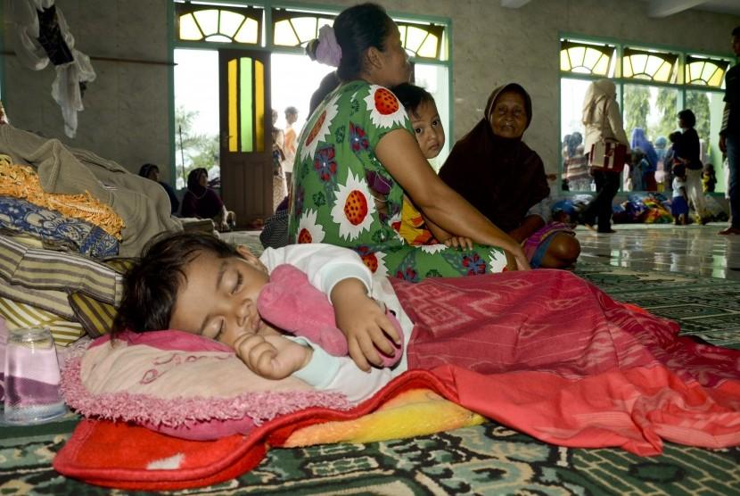 Seorang bocah tertidur lelap di posko pengungsian korban banjir bandang di masjid Baitul Hamid di Kelurahan Penaraga, Kota Bima, NTB, Senin (26/12).