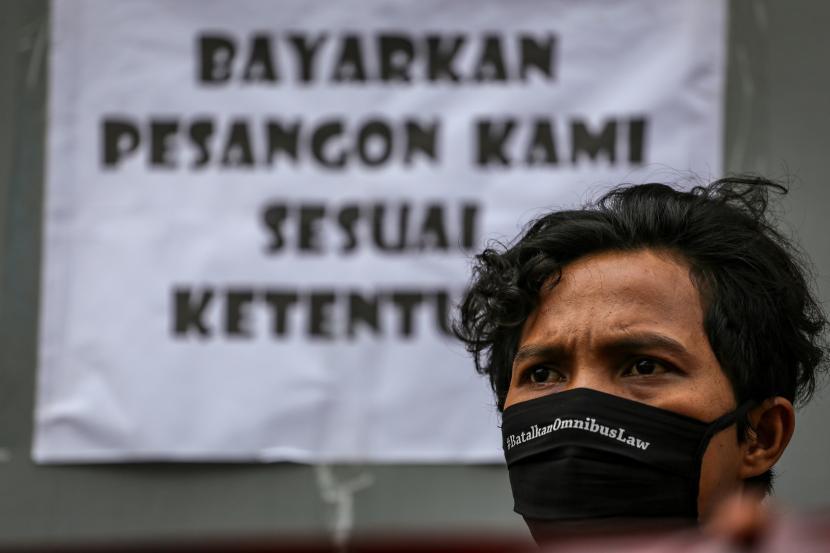 Seorang buruh menggelar aksi unjuk rasa di depan pabriknya di Benda, Kota Tangerang, Banten, Jumat (1/5/2020). Dalam aksi untuk memperingati Hari Buruh Internasional itu, massa menolak RUU Omnibus Law serta meminta pemerintah dan pengusaha untuk menjamin kelangsungan hidup buruh.