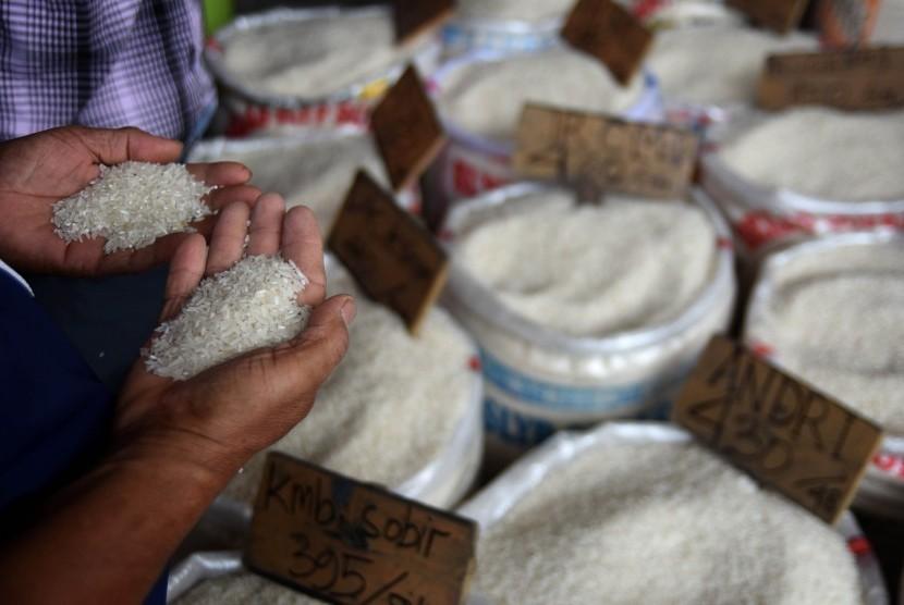 Seorang calon pembeli membandingkan dua kualitas beras yang dijual di Pasar Induk Beras Cipinang, Jakarta, Senin (20/5/2019).