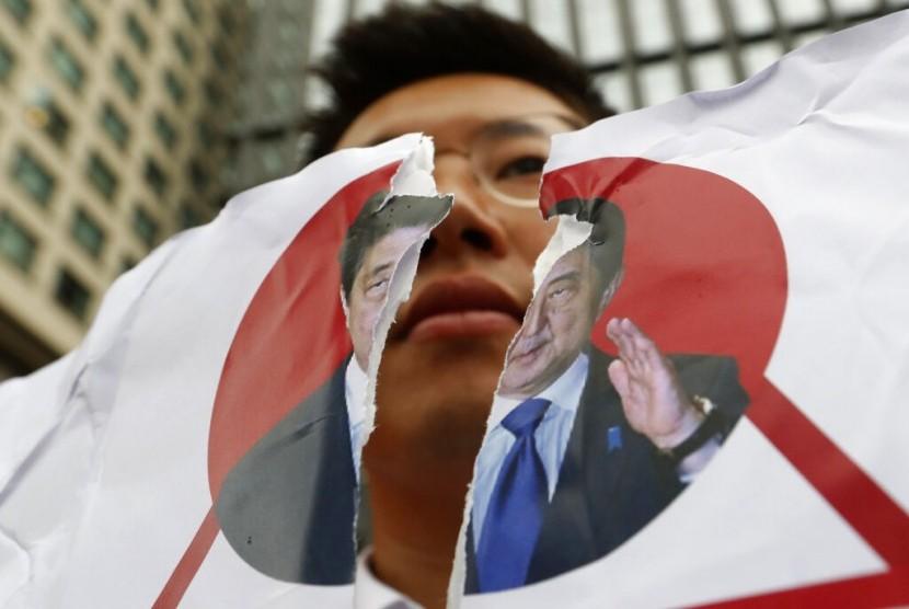 Seorang demonstran Korea Selatan (Korsel) merobek foto Perdana Menteri Jepang Shinzo Abe di depan Kedubes Jepang di Seoul, Rabu (17/7). Protes dilakukan mengecam keputusan Jepang membatasi ekspor ke Korsel.