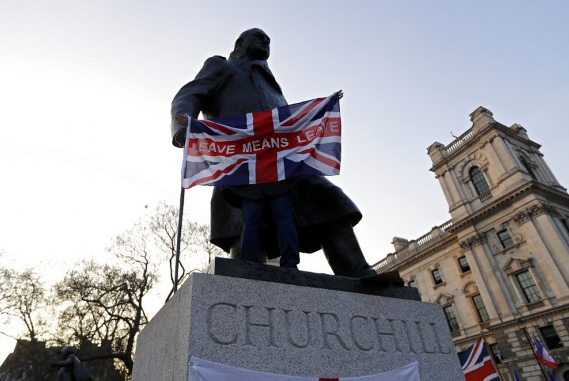 Seorang demonstran membawa bendera bertuliskan 'Leave means leave' di Patung Winston Churchill di London, Jumat (29/3). Demonstran pro Brexit melakukan aksi usai keputusan Uni Eropa yang menunda eksekusi Brexit.