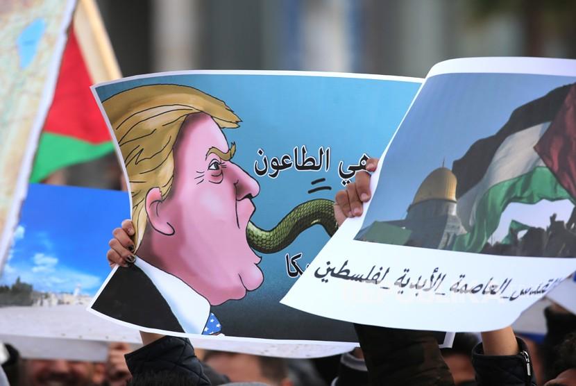 Seorang demonstran memegang poster kartun  Presiden AS dan sebuah foto kubah batu di dalam Masjid Al-Aqsa  yang bertuliskan Yerusalem adalah ibukota abadi Palestina dan Amerika adalah sebuah bencana ,di luar Kedutaan Besar AS di Amman, Yordania,