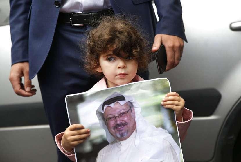 Seorang gadis memegang poster dengan foto penulis Arab yang hilang Jamal Khashoggi, selama protes dekat konsulat Arab Saudi di Istanbul,