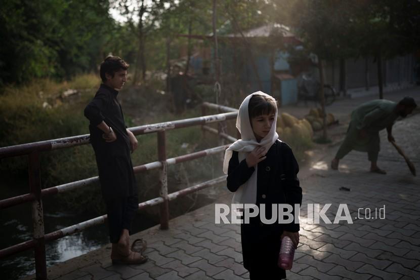 Seorang anak perempuan menunggu teman-temannya saat mereka berjalan ke sekolah di Kabul, Afghanistan, Ahad (12/9).