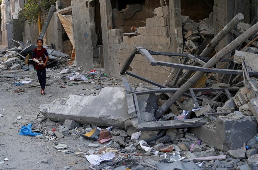 Seorang gadis Palestina berjalan di antara puing-puing sebuah bangunan yang runtuh setelah terkena serangan udara selama perang 11 hari antara penguasa Hamas Gaza dan Israel Mei lalu, di Kamp Pengungsi Maghazi, Jalur Gaza tengah, Senin, 12 Juli 2021.