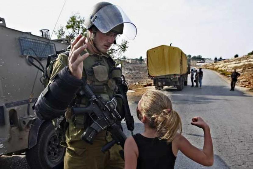 Seorang gadis Palestina mencoba meninju seorang tentara Israel saat unjuk rasa memprotes perluasan permukiman Yahudi di desa Halamish, dekat Ramallah, Jumat (2/11).