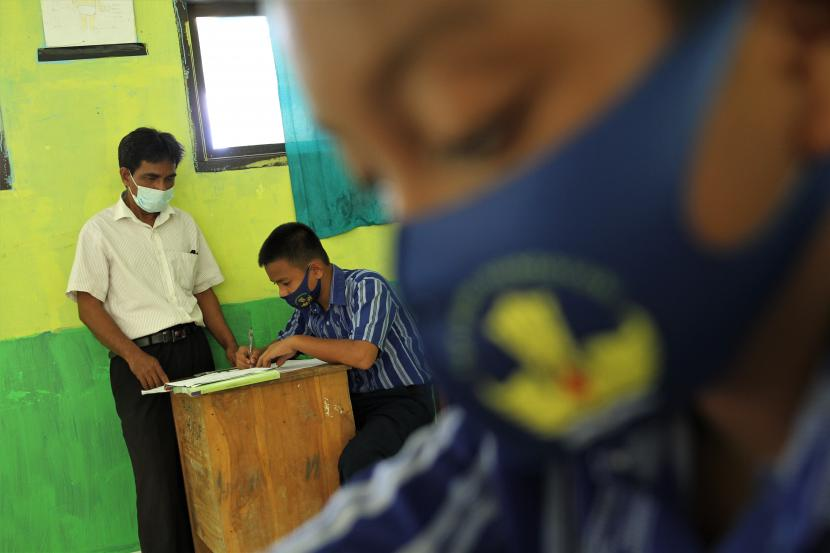 Seorang guru dan murid-muridnya mengenakan masker saat uji coba proses belajar mengajar secara tatap muka