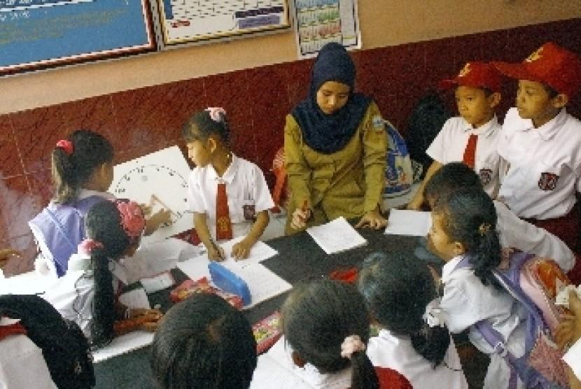 Seorang guru memberikan materi pelajaran kepada siswa kelas 2 SD.