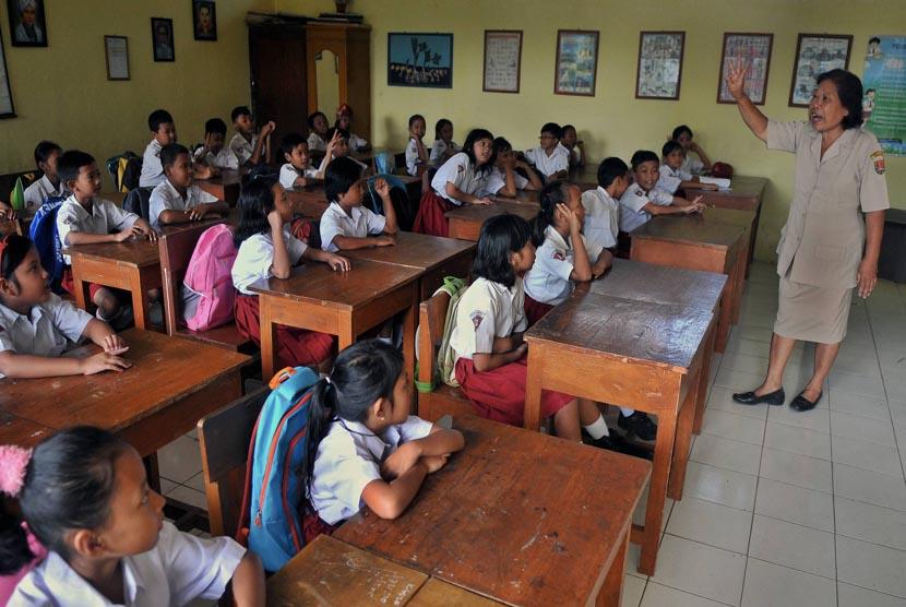 Seorang guru mengajar di kelas.   (ilustrasi)