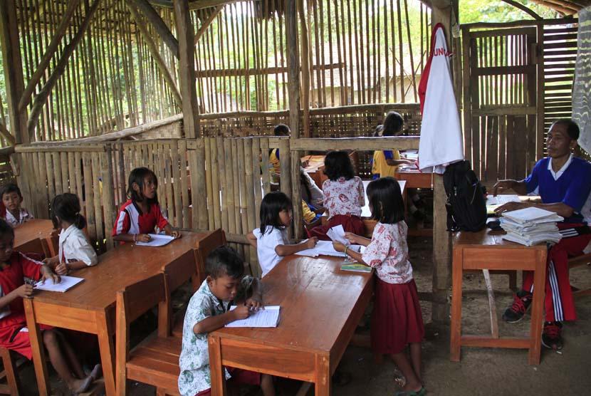 Seorang guru mengajar dua kelas sekaligus di ruangan terbuat dari bambu di SD Negeri Girijagabaya, di Kampung Sinarjaya, Muncang, Lebak, Banten, Rabu (27/11). (Antara/Asep Fathulrahman)