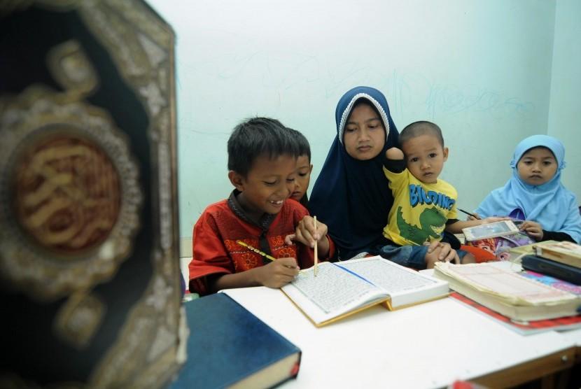 Seorang guru mengajarkan anak muridnya mengaji. Pemerintah Kota Surabaya akan memberikan insentif untuk guru ngaji sebesar Rp 300 ribu per bulan.