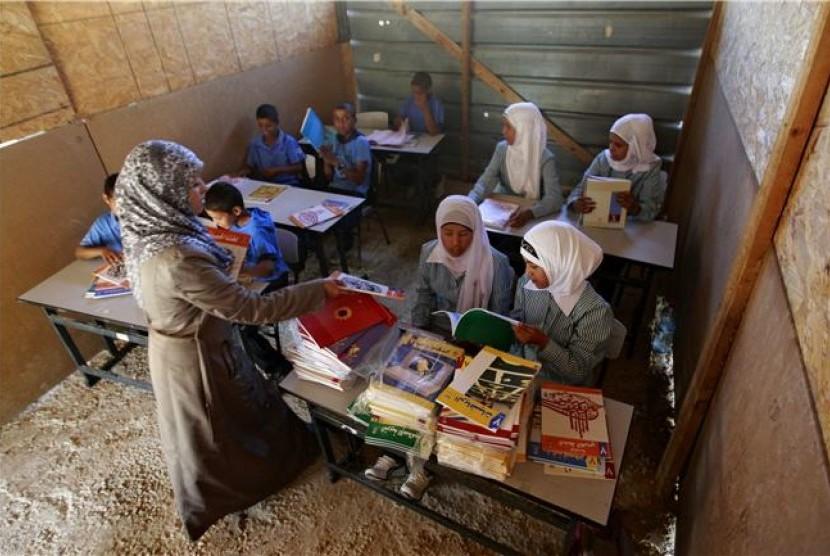 Seorang guru Palestina mengajar di sebuah sekolah di Khan al-Ahmar, Tepi Barat, pada Ahad (2/9).