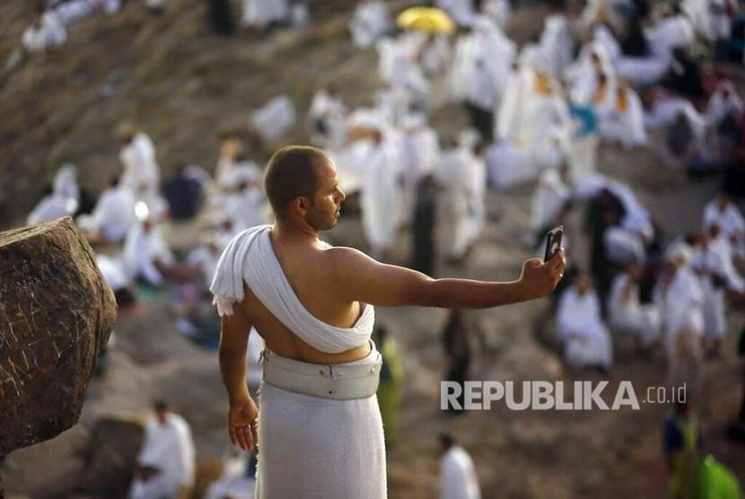 Seorang jamaah haji berswafoto di Jabal Rahmah saat berwukuf di Padang Arafah, Makkah, Arab Saudi, Sabtu (10/8). Sekitar 2 juta jamaah haji dari berbagai negara  berwukuf di tempat ini sebagai salah satu syarat sah berhaji.