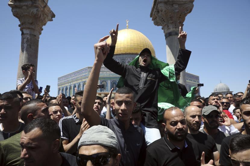 Seorang jamaah Muslim mengenakan bendera Hamas saat melakukan protes terhadap serangan udara Israel di Jalur Gaza setelah salat Jumat di Masjid Kubah Batu di kompleks Masjid Al-Aqsa di Kota Tua Yerusalem, Jumat, 14 Mei 2021.