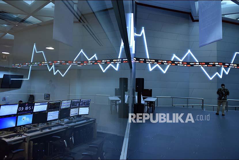 Seorang karyawan beraktivitas di dekat tayangan pergerakan Indeks Harga Saham Gabungan (IHSG) di gedung Bursa Efek Indonesia, Jakarta, Jumat (16/6). IHSG ditutup melemah sebesar 52,64 poin atau 0,91 persen menjadi 5.723,63 poin, dipicu sebagian investor yang masih merespon negatif kenaikan suku bunga Amerika Serikat.