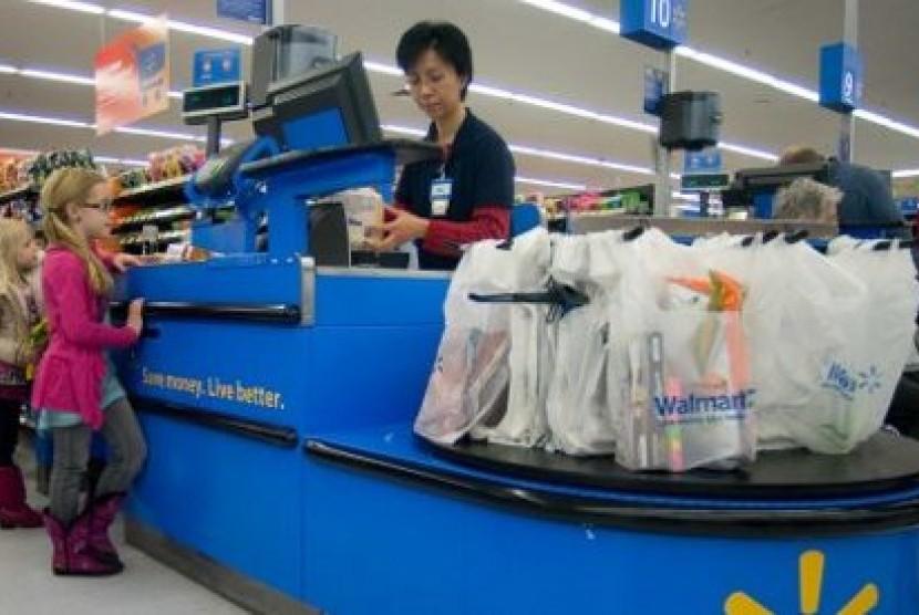 Seorang karyawan melayani konsumen di bagian kasir Wal-Mart (ilustrasi)