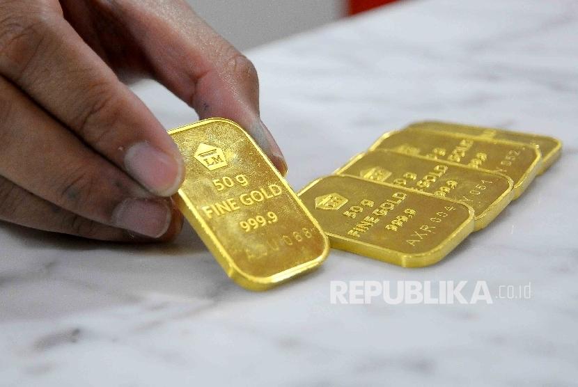 Seorang karyawati menunjukan emas batangan di salah satu bank di Jakarta, (ilustrasi).   Anggota Komisi III DPR, Arteria Dahlan, meminta Kejaksaan Agung mengusut tuntas skandal impor emas senilai Rp 47,1 triliun melalui Bandara Internasional Soekarno-Hatta, Banten.
