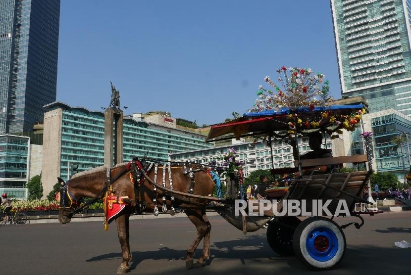 Seorang kusir delman nampak menunggu calon penumpang yang akan menggunakan jasa delmannya untuk berkeliling di kisaran bundaran Hotel Indonesia Jakarta, Ahad (2/7).