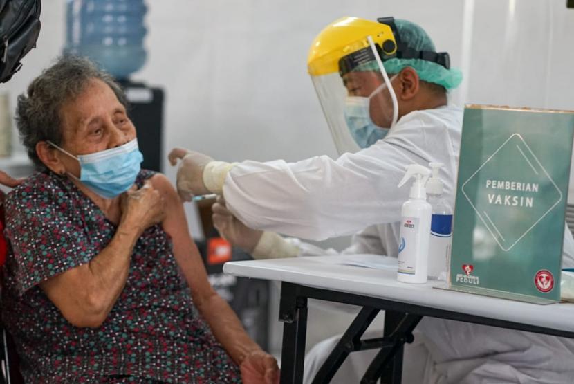 Seorang lansia mendapatkan suntikan vaksin Covid-19 dari petugas nakes.