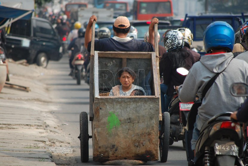 Seorang lelaki dari keluarga miskin mengangkut anak dan istrinya dengan gerobak. ilustrasi (foto: Raisan Al Farisi)