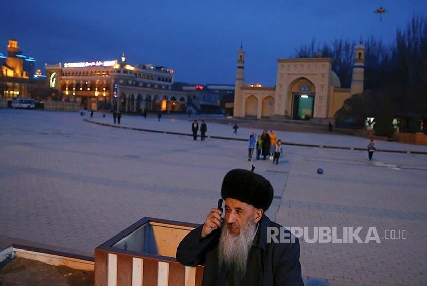 Diplomat Inggris Ungkap China Bongkar Kubah Masjid Dongguan. Seorang lelaki Uighur menggunakan ponsel di depan Masjid Id Kah di kota tua Khasgar, Daerah Otonomi Xinjiang Uighur, China.