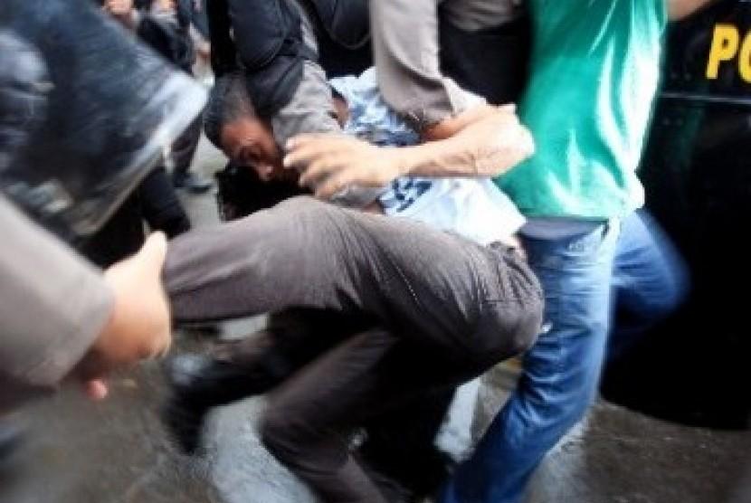 Seorang mahasiswa tertangkap dalam bentrok aparat dengan berbagai aliansi mahasiswa yang menolak kenaikan BBM di Kawasan Stasiun Gambir, Jakarta, Selasa (27/3).