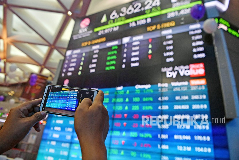 Seorang mengunjung memotret layar pergerakan Indeks Harga Saham Gabungan (IHSG) di Bursa Efek Indonesia, Jakarta, Jumat (28/6/2019).