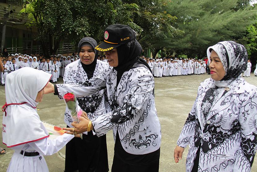 Seorang murid menghadiahkan bunga kepada gurunya saat upacara peringatan Hari Guru Nasional di SDN 1 Banda Aceh, Rabu (25/11).
